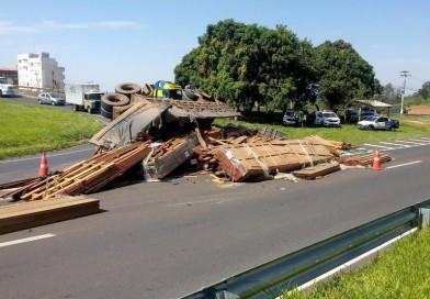 Caminhão carregado de madeira tomba e carga fica espalhada na pista em rodovia de Marília